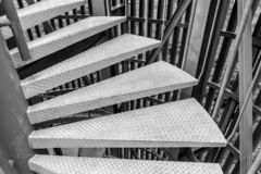 Steel spiral staircase. Black and white of Steel spiral staircase with steel battens on natural background royalty free stock photography