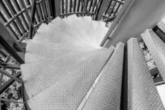 Steel spiral staircase. Black and white of Steel spiral staircase with steel battens on natural background stock photo