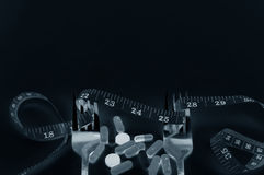 Steel Spoon fork, pills and measuring tape Stock Images