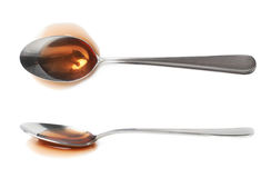 Steel spoon in a puddle of wine vinegar Stock Photography