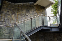Steel stairway outside building with grey brick wall Royalty Free Stock Photography