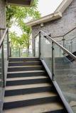 Steel stairway outside gray brick building Stock Photo