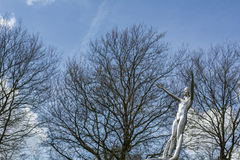 Steel statue of naked woman with bare trees Royalty Free Stock Photo