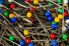 Steel straight pins/push pins for sewing, in a box with multicolored plastic ball heads. The extreme macro allows the ability to see the polish and the use of royalty free stock photo