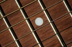 Steel strings and fretboard on classical guitar. Closeup of steel strings and mahogany wood fretboard with white dot inlay on classical guitar stock photography