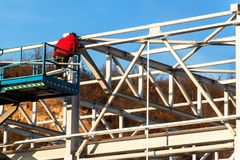 The steel structure is under construction. Installation of metal halls. Work at height. A sunny day at a construction site. Royalty Free Stock Photo