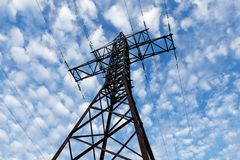 High voltage support. Steel support of a high-voltage transmission line against a cloudy sky Stock Photo