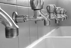 Steel taps in white ceramic sink Stock Photo
