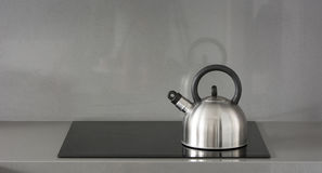 Steel teapot on induction stove Royalty Free Stock Images