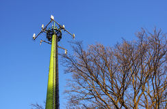 Steel telecommunication tower with antennas over blue sky and trees Stock Photos