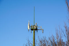 Steel telecommunication tower with antennas over blue sky and trees Royalty Free Stock Images