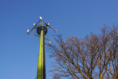 Steel telecommunication tower with antennas over blue sky and trees Royalty Free Stock Photography