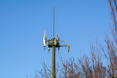 Steel telecommunication tower with antennas over blue sky and trees Stock Image