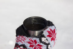 A cup with tea in a hand in a mitten. A steel thermos cap with tea in a hand in a mitten outdoors in winter Royalty Free Stock Photo