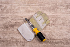 Steel tool and working glove on a wooden table Stock Photo