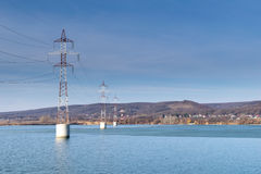Steel tower of High Voltage. Transmission line over the river. Arges Romania Stock Photos