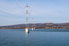 Steel tower of High Voltage. Transmission line over the river. Arges Romania Royalty Free Stock Photo