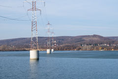 Steel tower of High Voltage. Transmission line over the river. Arges Romania Royalty Free Stock Photos