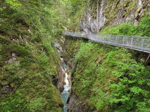 Steel trail at rock wall in gorge Stock Photography
