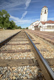 Steel train tracks lead past a train depot. Railroad tracks lead past a depot with blue sky and clouds Stock Images