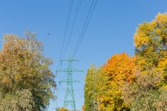 Steel transmission tower of overhead power line among of forest. Steel lattice transmission tower of overhead power line among of the autumn forest on background stock photos