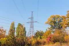 Steel transmission tower of overhead power line among of forest. Steel lattice transmission tower of overhead power line among of the autumn forest on background stock images
