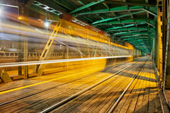 Steel Truss Bridge with Tram Light Trail Stock Photo