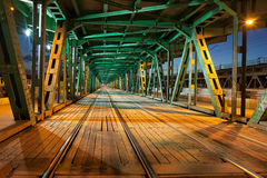 Steel Truss Bridge Tramway at Night. Tramway with two tracks in the lower part of the steel truss Gdanski Bridge in Warsaw, Poland, night illumination, vanishing Stock Photography