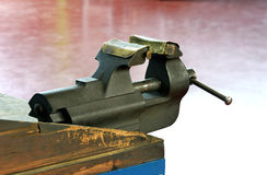 Steel vice mounted on a wooden workbench Stock Images