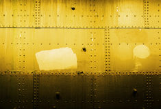 Steel wall in yellow tone. A yellow-tinted picture of a steel wall, the pieces held together by small nuts and bolts. This is probably the hull of a ship royalty free stock images