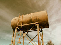 Steel Water Tank. Weathered water tank sits atop tall platform.  Cloudy sky is backdrop. Desert feeling Royalty Free Stock Images