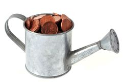 Steel watering can filled with coins on a white background stock photos