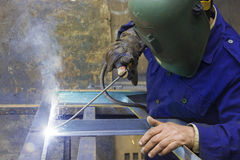 Steel Welder. Close up for a welder wearing gloves and Protective Mask fusing  metal pieces by heating the surfaces to the point of melting using welding machine Stock Image