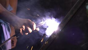 Steel welders with electric welding. No self-defense, unprotected with gloves. Slow motion.