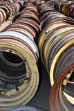 The steel wheels and rims of old tractors and vintage machinery are in rows found in a field royalty free stock photo