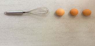 Steel whisk and eggs lined in a row on grey background. With space for text stock images