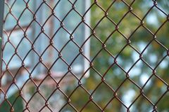 Steel wire net fence with blurred green background royalty free stock image