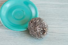 Steel wool with dish on wood table. Cleanning tool stock photo
