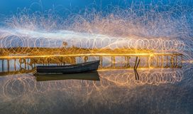 Steel Wool Light Painting in a cloudy morning. Steel Wool Light Painting on wooden pontoon and fishing boat in a cloudy morning Royalty Free Stock Images