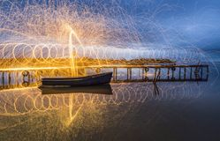 Steel Wool Light Painting in a cloudy morning. Steel Wool Light Painting on wooden pontoon and fishing boat in a cloudy morning Royalty Free Stock Photos