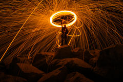 Steel wool photography. Guy with steel wool that make sparks while standing on rocks Stock Images
