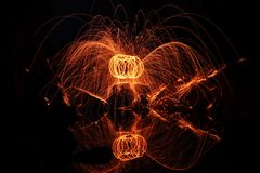 Steel Wool Reflection. A fiery, shot of spinning steel wool over a riverbed stock image
