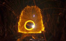 Steel Wool Sparks. Spinning Steel Wool in old train tunnel with shower of hot sparks and rock walls royalty free stock images