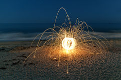 Steel Wool Sparks on the Beach. Spinning lit steel wool sparks on the beach at high speed stock images