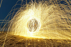 Steel Wool Sparks on the Beach. Spinning lit steel wool sparks on the beach at high speed royalty free stock photography