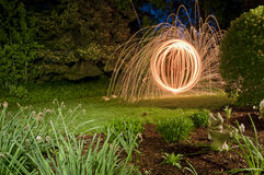 Steel Wool Sparks in the garden. Spinning lit steel wool sparks in the garden at night royalty free stock photo