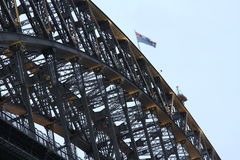 Steel work bridge construction. Low-angle image of the steel-girder construction of the Sydney Harbour Bridge with the Australian flag on the top Stock Image
