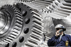 Steel worker with large cogwheels machinery Stock Photos