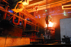 Steel works, crane with stove busket. Crane with stove busket at steel plant stock photos