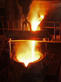 Steel Works steel production. Molten, glowing, yellow, white, metal pouring in kovsh.ognennye sparks fly Royalty Free Stock Image